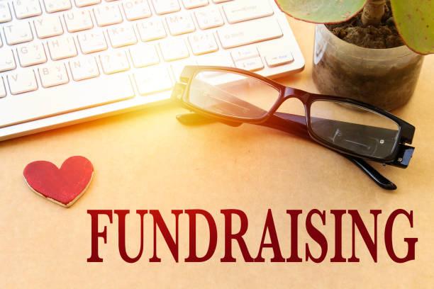 fundraising-fonds kapital hilfe beratung concept.white tastatur und brillen, topfpflanze, herz aus holz - spenden sammeln stock-fotos und bilder