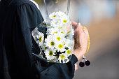 葬儀と日本の墓への訪問.シニアの女性は、黒い喪服で先祖の魂を崇拝します。私は手に白い菊の束とビーズを保持しています。