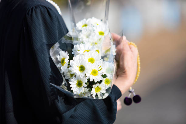 a funeral and visit to a grave of japan. the woman of the senior worships the ancestral soul in a black mourning dress. i hold white chrysanthemum bunch and beads in a hand. - funerale foto e immagini stock