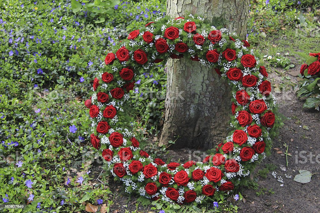 Funeral red rose wreath near a tree stock photo