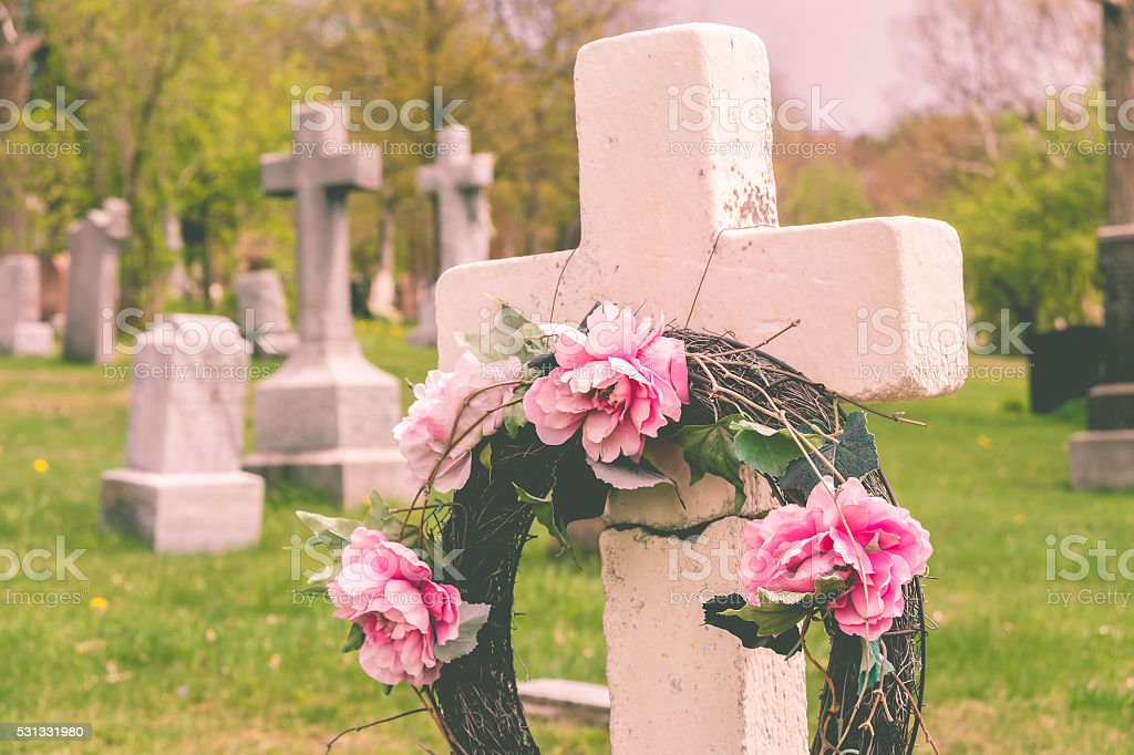 Funeral wreath with pink flower on a cross stock photo