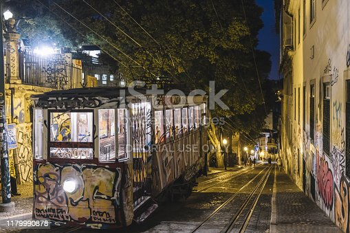 Lisbon, Portugal – august, 2019: Funicular of Gloria (Elevador da Gloria) painted with graffiti up the Gloria street in the night light