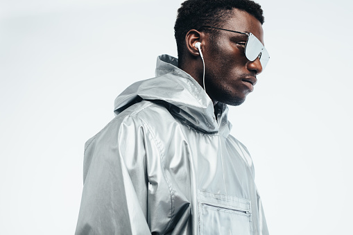 Handsome african man in silver hooded shirt, sunglasses and earphones against gray background. Funky young african american man.