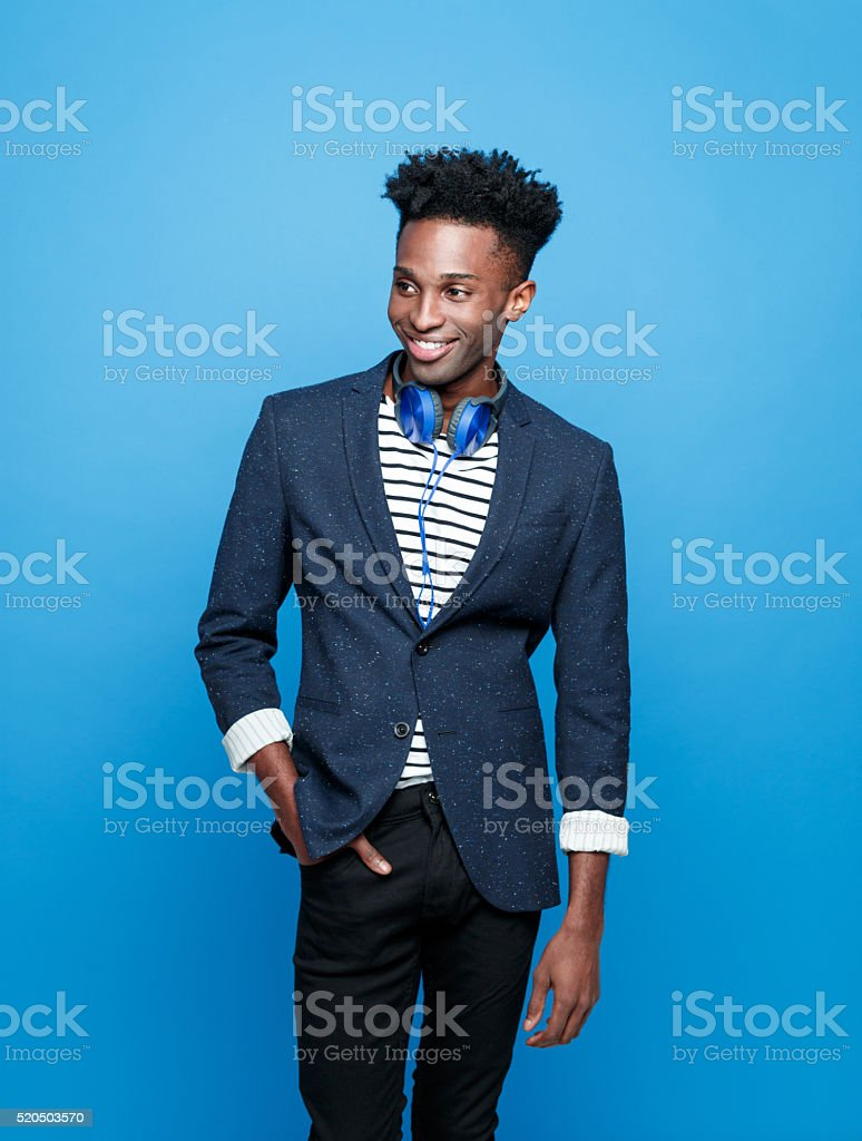 Funky afro american guy against blue background Studio portrait of fashionable afro american young man wearing striped top, jacket and headphone, looking away and smiling. Studio portrait, blue background. Adult Stock Photo
