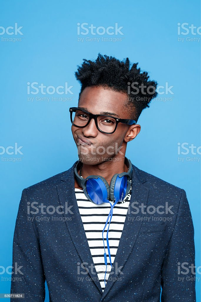 Funky afro american guy against blue background Studio portrait of fashionable afro american young man wearing striped top, navy blue jacket, nerd glasses and headphone, making face. Studio portrait, blue background. Adult Stock Photo