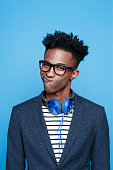 Studio portrait of fashionable afro american young man wearing striped top, navy blue jacket, nerd glasses and headphone, making face. Studio portrait, blue background.