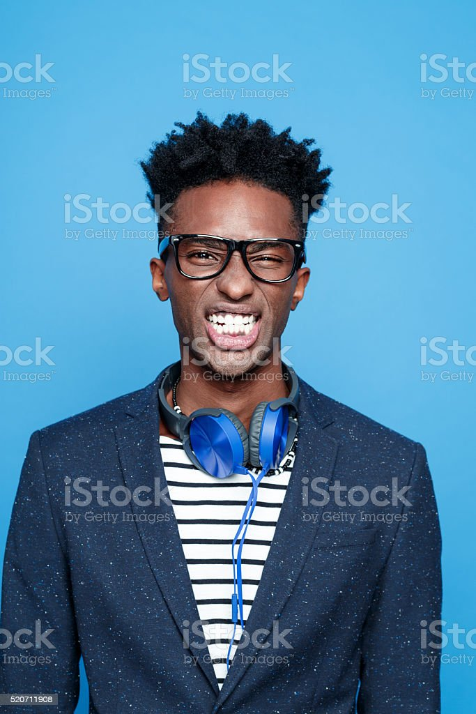 Funky afro american guy clenching teeth Studio portrait of fashionable afro american young man wearing striped top, navy blue jacket, nerd glasses and headphone, clenching teeth. Studio portrait, blue background. Adult Stock Photo