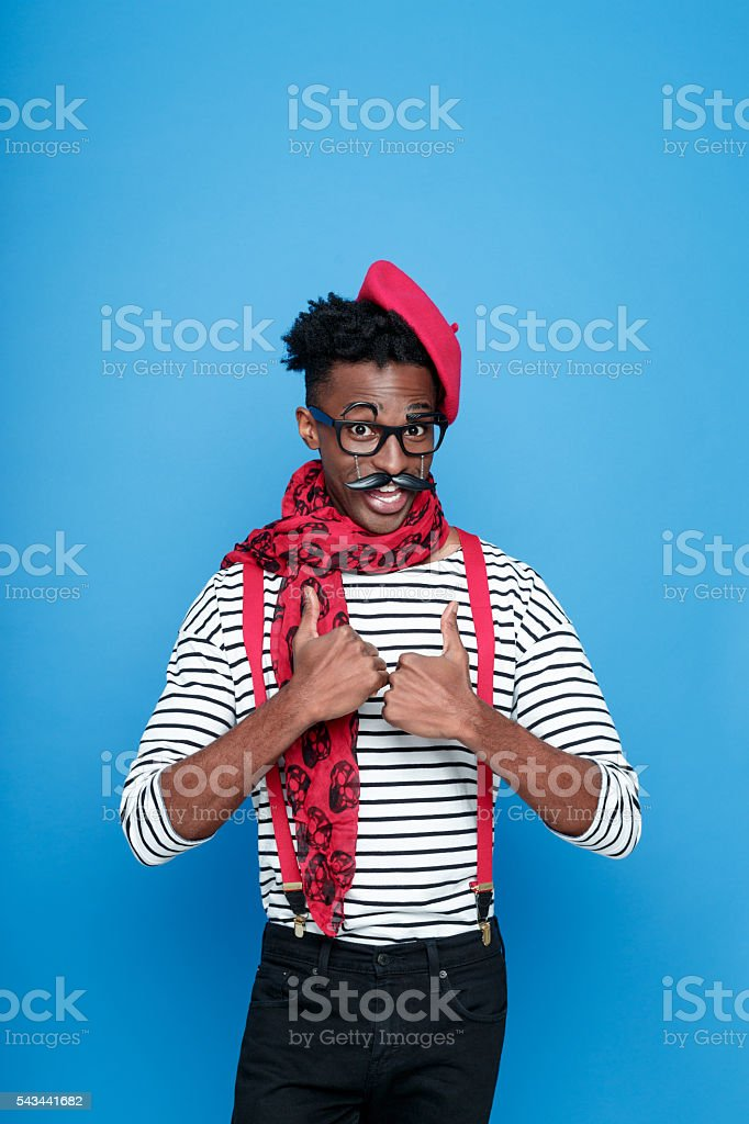 Funky afro american guy in a french outfit Portrait of excited afro american guy wearing striped long sleeved t-shirt, red suspenders, beret and neckscarf, smiling at camera with thumbs up. Studio shot, blue background.  Adult Stock Photo