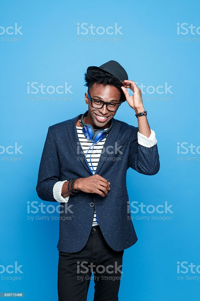 Funky afro american guy in fashionable outfit Studio portrait of successful afro american young man wearing striped top, navy blue jacket, nerd glasses, hat and headphone, smiling at camera. Studio portrait, blue background. Adult Stock Photo