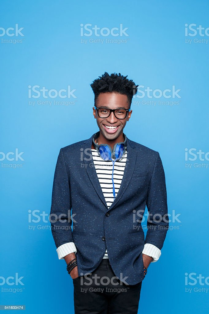 Funky afro american guy in fashionable outfit Studio portrait of happy afro american young man wearing striped top, navy blue jacket, nerd glasses and headphone, laughing at camera. Studio portrait, blue background. Adult Stock Photo