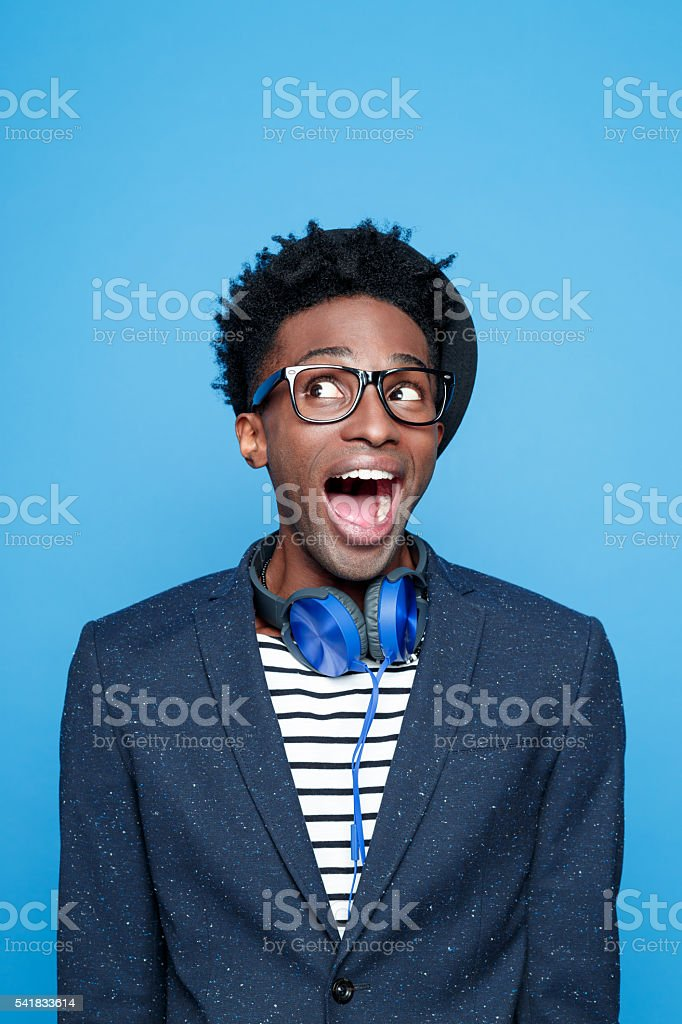 Funky afro american guy in fashionable outfit Studio portrait of excited afro american young man wearing striped top, navy blue jacket, nerd glasses, hat and headphone. Studio portrait, blue background. Adult Stock Photo