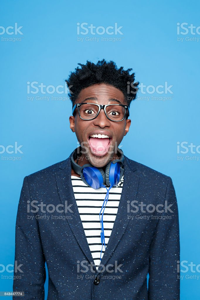 Funky afro american guy in fashionable outfit Studio portrait of excited afro american young man wearing striped top, navy blue jacket, nerd glasses and headphone, laughing at camera. Studio portrait, blue background. Adult Stock Photo