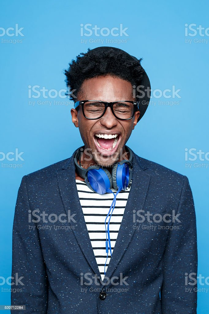 Funky afro american guy screaming Studio portrait of angry afro american young man wearing striped top, navy blue jacket, nerd glasses, hat and headphone, shouting. Studio portrait, blue background. Adult Stock Photo