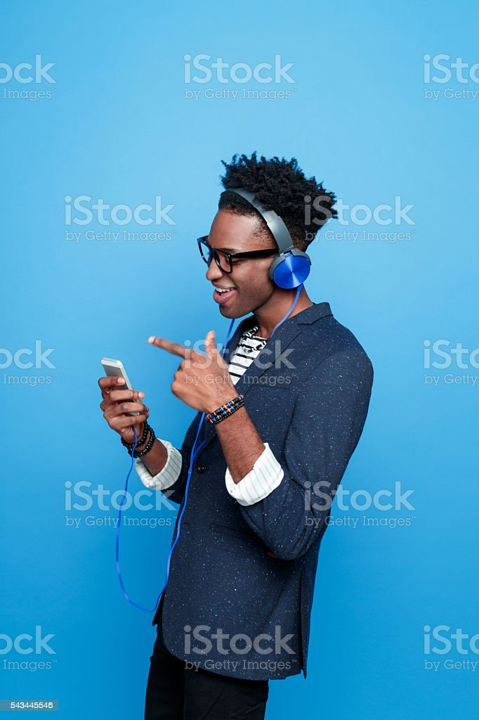 Funky afro american guy using a smart phone Studio portrait of funky afro american young man wearing striped top, navy blue jacket, nerd glasses and headphone, using a smart phone. Studio portrait, blue background. Adult Stock Photo