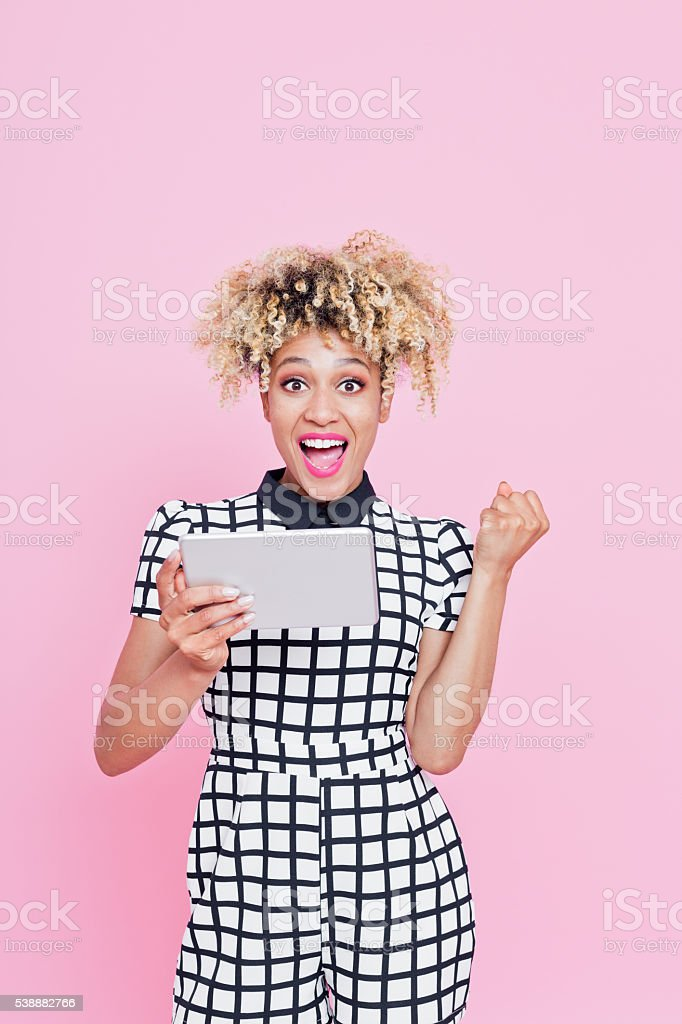Funky afro american woman using a digital tablet Studio portrait of excited afro american young woman wearing white and black grid check playsuit. Using a digital tablet. Studio portrait, pink background. 20-29 Years Stock Photo