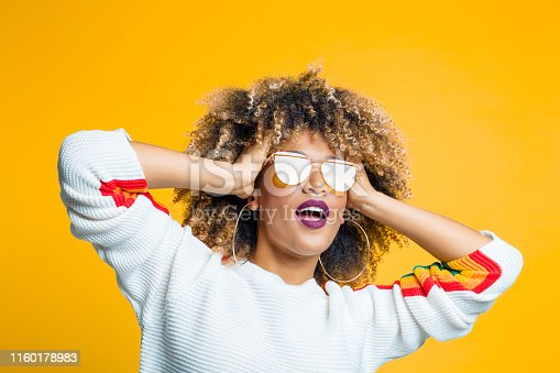 Portrait of funky young afro girl standing against yellow background with hand in hair and looking away