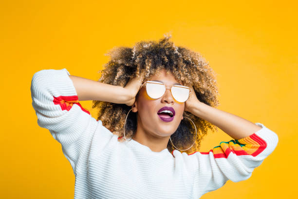Funky afro girl against yellow background stock photo