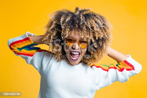 657442382istockphoto Funky afro young woman against yellow background 1094450730