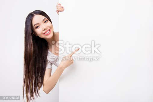 933380808istockphoto Funky asian young girl with long hair is looking out of a blank white clean banner or billboard, she is pointing on empty copy space, she is isolated on grey background 926176198