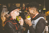 Afro american young man and blonde young woman eating burgers in the pub, making funny faces. Dark tone.
