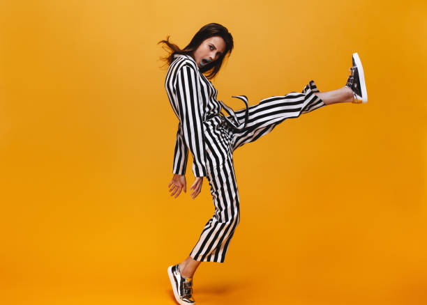 Funky female on orange background Full length of young woman in jumpsuit kicking over orange background. Funky female with raised leg looking at camera. funky stock pictures, royalty-free photos & images
