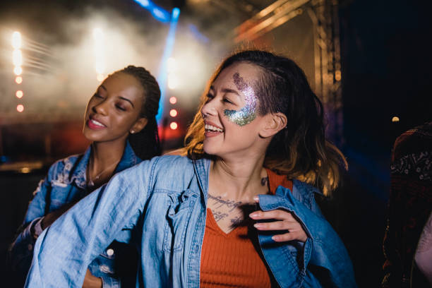 Funky Festival Dancing young women are dancing in a crowd at a music festival. college fair stock pictures, royalty-free photos & images