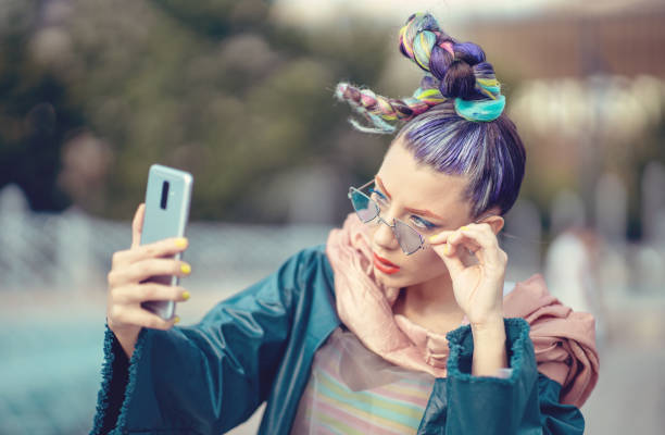 Funky girl with bizarre fashion style hair taking selfie on street stock photo