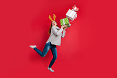 Funky lady santa delivery, service holding too much giftboxes wear head horns and knitted pullover isolated red background