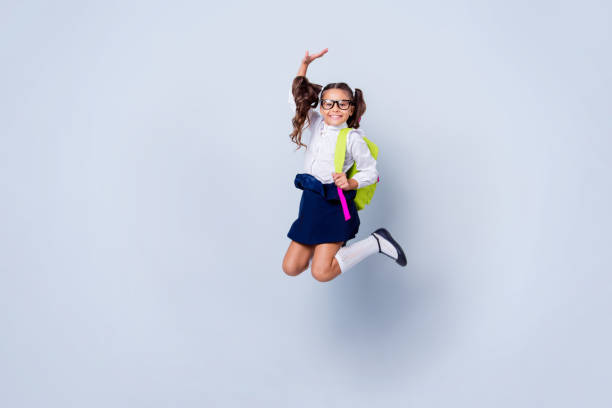 funky nice cute genius positive cheerful lovely small little girl with curly pigtails in white formal blouse shirt, skirt, jumping, raising hand up, fooling, yellow bag. isolated over grey background - униформа стоковые фото и изображения