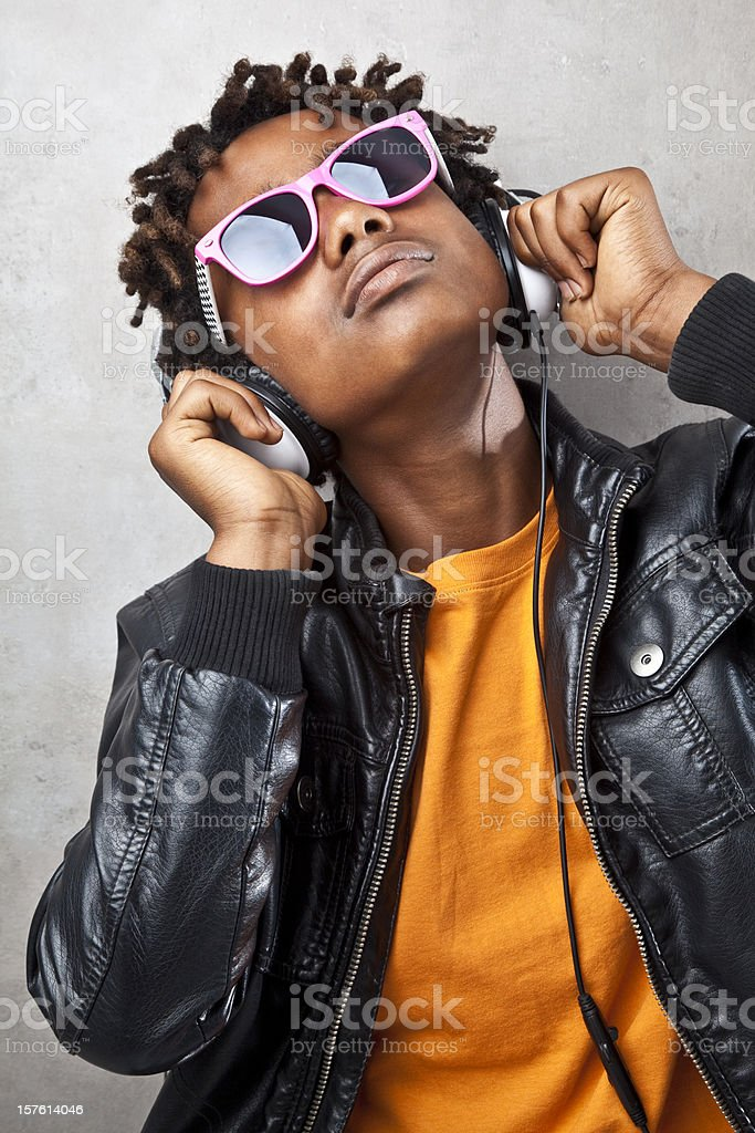 Funky teenager listening to headphones stock photo