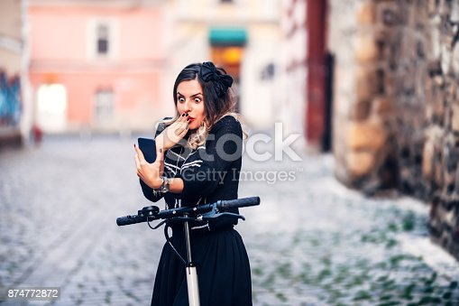 874772840istockphoto Funky woman making faces while looking at camera. Young woman taking photographs with smartphone 874772872