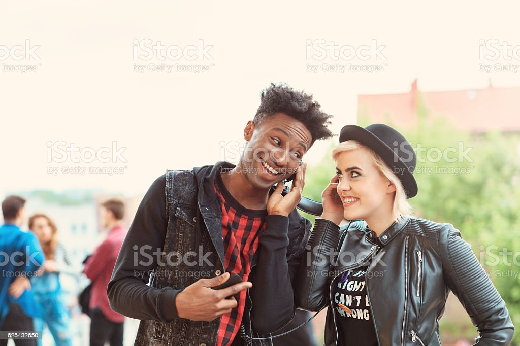 Funky young couple listening to music outdoor Outdoor portrait of funky young couple - afro amercian cool guy and beautiful blonde woman, listening to the music together. Group of people in the background. 20-29 Years Stock Photo