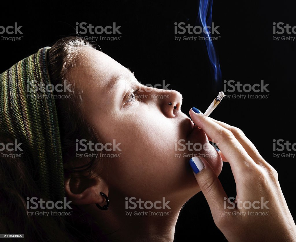 Funky young rebel puffs on a joint of cannabis stock photo