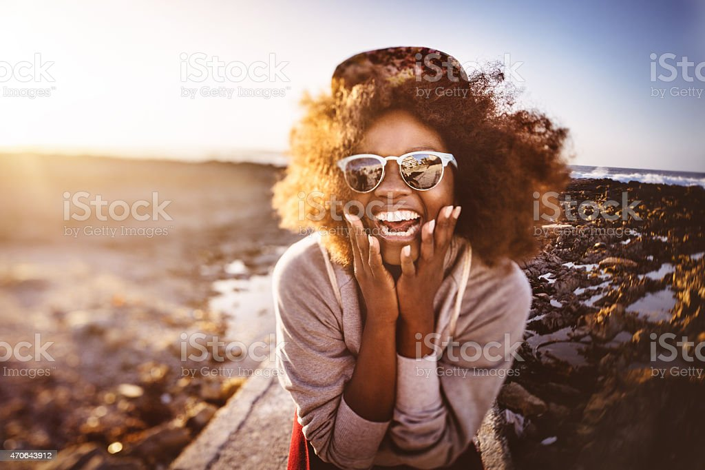 Fun-loving African American teenage hipster at the beach laughing stock photo