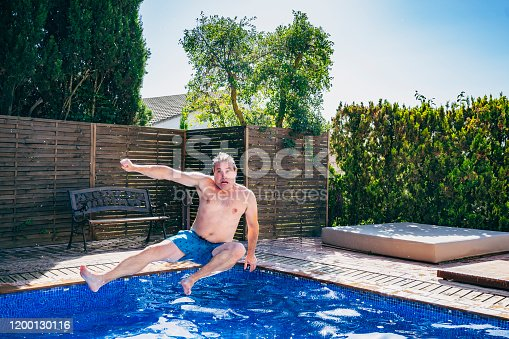 Carefree Spanish male in late 40s jumping into swimming pool with arms and legs outstretched in flying kick mid-air.