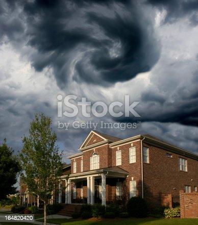 A tornado forms over a row of traditional, Brick homes.