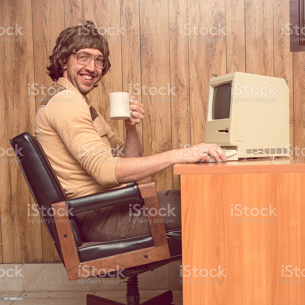 Funny 1980s Computer man at desk with coffee bildbanksfoto