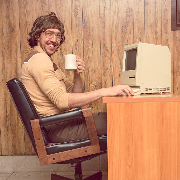 funny 1980s computer man at desk with coffee - desktop foto stock-fotos und bilder