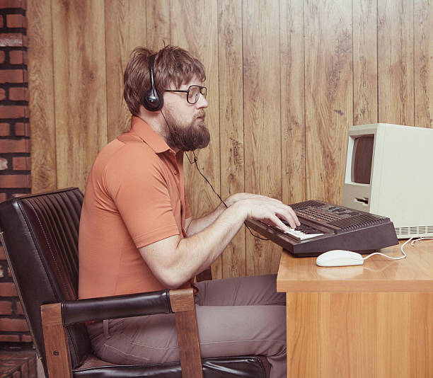 Funny 1980s man playing synthesizer DAW Nerdy 1980s themed photo of man playing a synthesizer keyboard with his retro computer recording music. Wearing Headphones synthesizer stock pictures, royalty-free photos & images