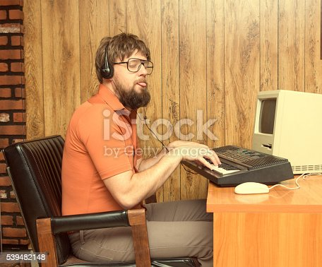 Nerdy 1980s themed photo of man playing a synthesizer keyboard with his retro computer recording music. Wearing Headphones