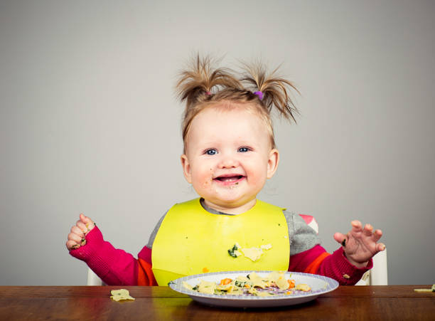 Funny 9 month old eating pasta stock photo
