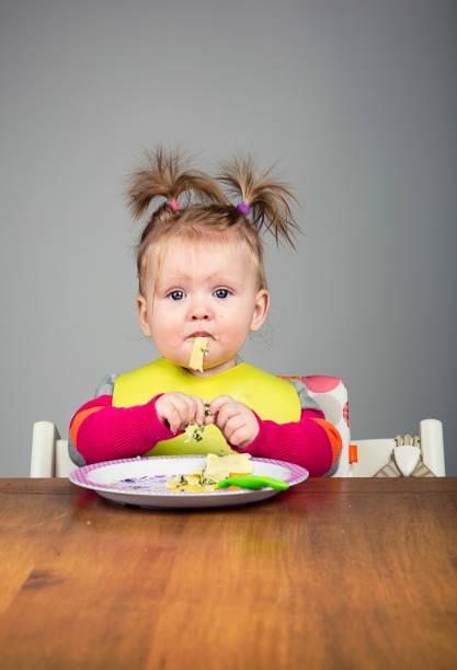 lustige 9 monate altes essen nudeln - kinderstuhl und tisch stock-fotos und bilder
