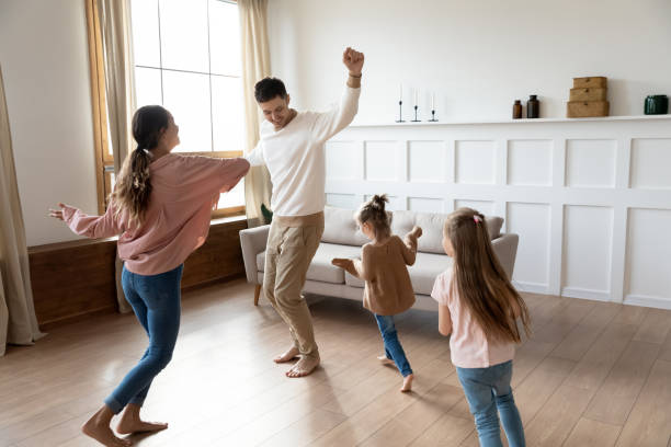 Funny active parents and children daughters dancing in living room Funny active family of four young adult parents and cute small children daughters dancing together in living room interior, carefree little kids with mum dad having fun laughing enjoy leisure at home activity stock pictures, royalty-free photos & images