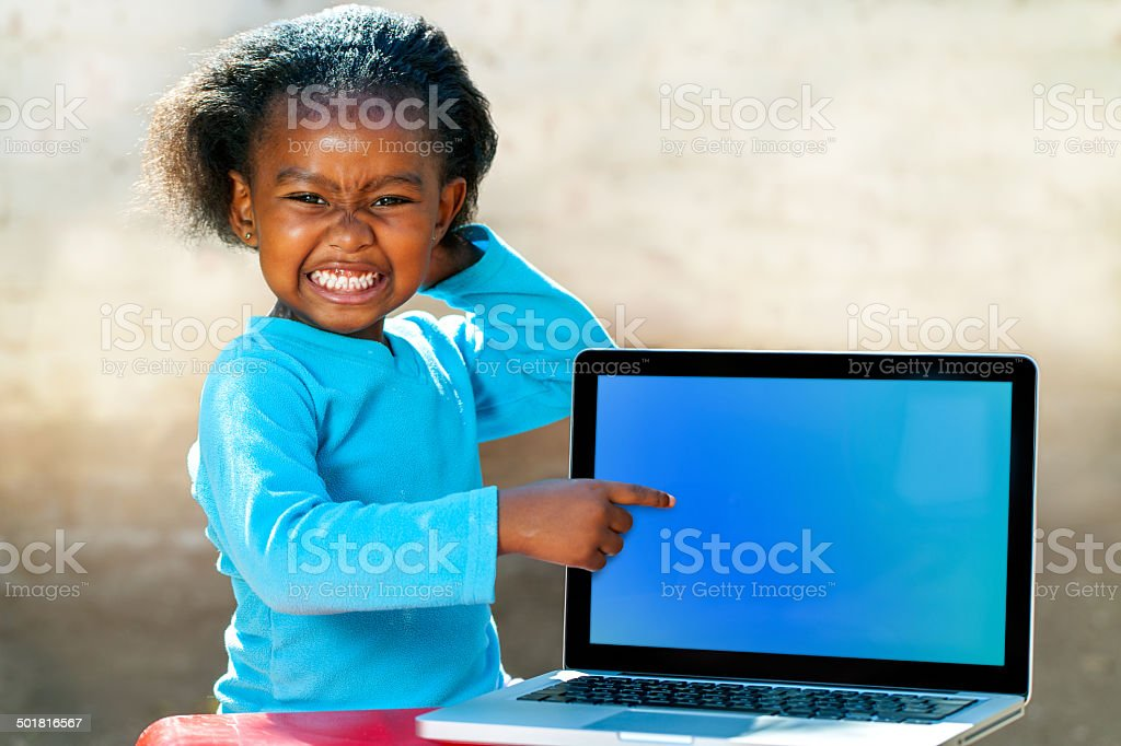 Funny african girl pointing at blank screen. stock photo