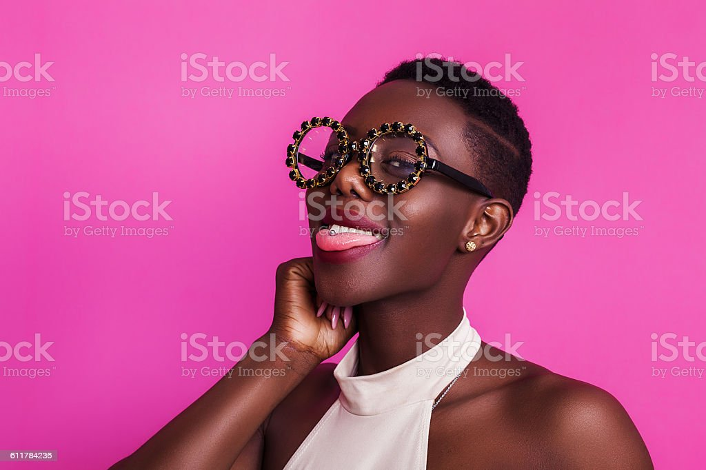 Funny african girl with tongue stuck out wearing strange glasses stock photo
