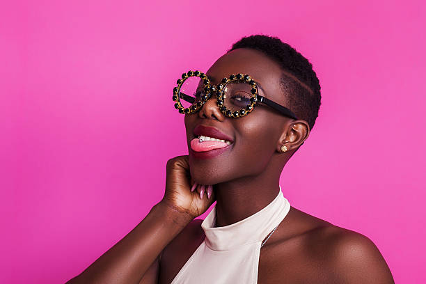funny african girl with tongue stuck out wearing strange glasses - ausgefallene frisuren stock-fotos und bilder