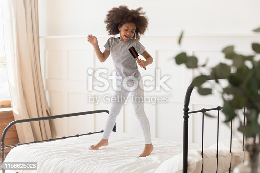 Happy funny cute little african american kid girl jumping on bed singing in microphone hairbrush at home, small mixed race child having fun dancing to music playing in bedroom alone in the morning