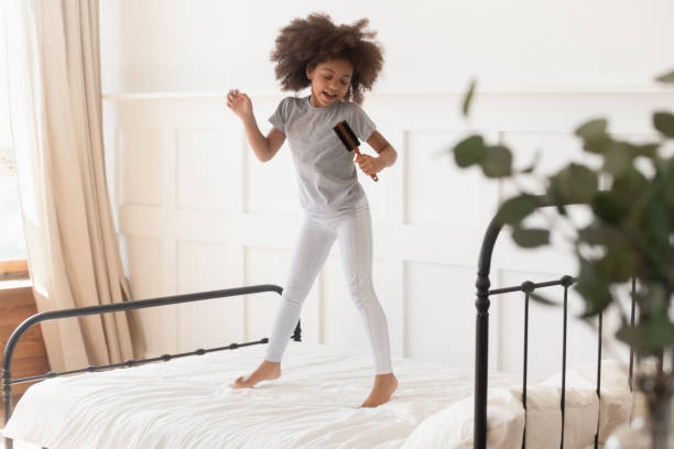 Funny african kid girl jumping on bed singing in hairbrush Happy funny cute little african american kid girl jumping on bed singing in microphone hairbrush at home, small mixed race child having fun dancing to music playing in bedroom alone in the morning girl bedroom stock pictures, royalty-free photos & images