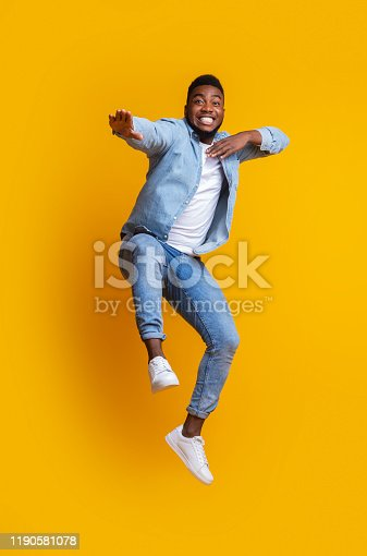 istock Funny afro guy jumping and making karate moves on yellow background 1190581078
