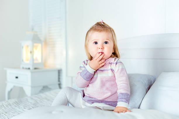 lustig begeistert blondes mädchen sitzt auf dem bett im schlafzimmer - nachttischleuchte touch stock-fotos und bilder